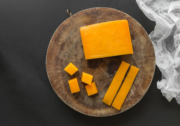 Bloc, tranches et cubes de fromage cheddar