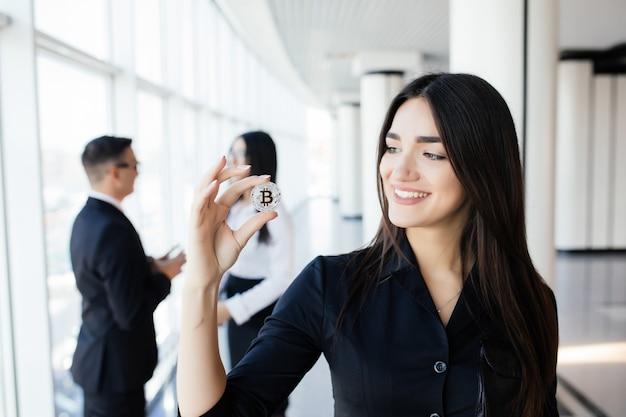 Blockchain et concept d'investissement. business woman leader holding bitcoin devant son équipe de discussion sur le bureau.