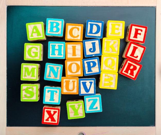 Blocs d'alphabet en bois avec des lettres sur une planche de bois