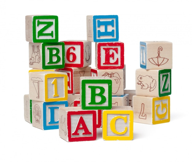 Blocs d'alphabet coloré empilés dans un désordre isolé sur blanc