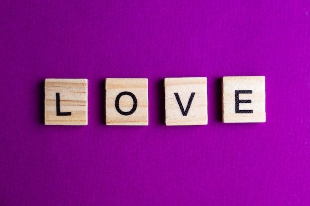 Blocs d'alphabet avec des lettres sur fond rose. inscription love.
