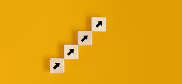 Des blocs de bois carrés sont placés sur un fond jaune, sur les blocs de bois il y a des contrats de flèche et s'alignent. concept de bloc de bois, bannière avec espace de copie pour le texte, affiche, modèle de maquette.