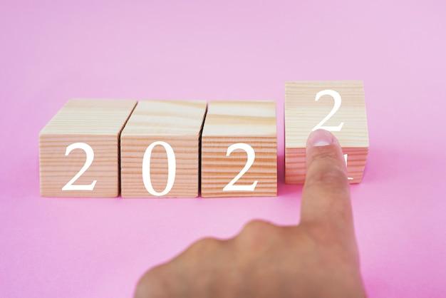 Blocs de bois changeant à la main avec le numéro 2021 à 2022. concept de nouvel an. espace de copie.