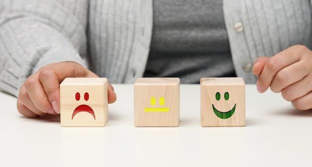 Blocs de bois avec différentes émotions du sourire à la tristesse et la main d'une femme. concept d'évaluation de la qualité d'un produit ou d'un service, état émotionnel, avis des utilisateurs