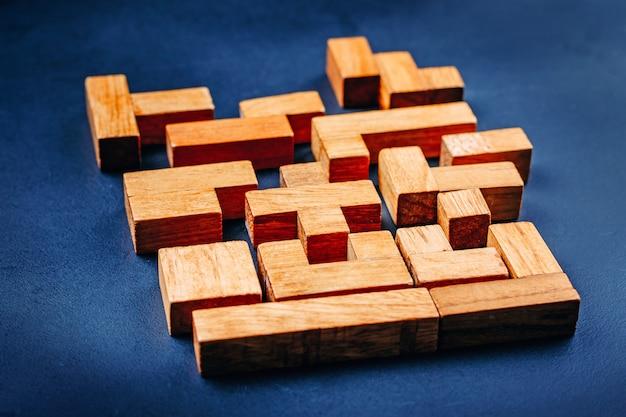 Blocs de bois de différentes formes géométriques sur un fond sombre.