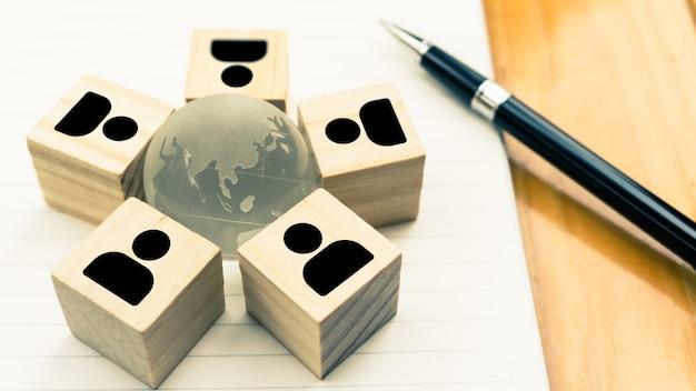 Des blocs de bois icône homme d'affaires se trouvent dans le monde entier cristal sur ordinateur portable avec un stylo noir.