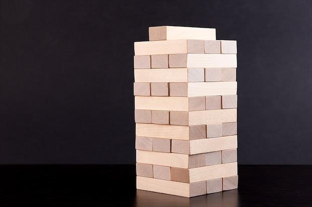 Blocs de bois sur un jeu de stratégie sombre comme un plan d'affaires pour le travail d'équipe