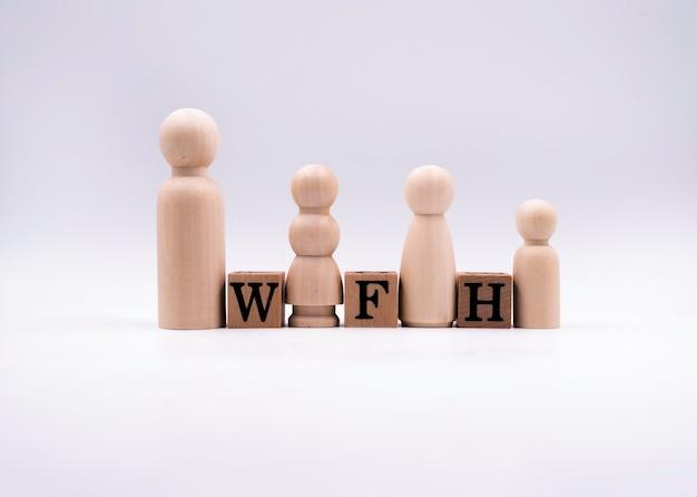 Blocs de bois, avec les lettres w, f et h, l'orthographe est work from home et petite poupée