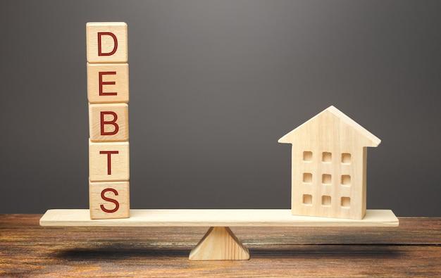 Blocs de bois avec le mot dettes et une maison miniature sur la balance.
