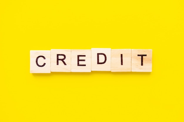Blocs de bois avec le mot de lettrage crédit sur le dessus du tableau jaune. concept commercial et financier.