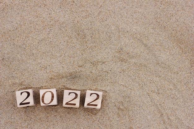 Des blocs de bois avec les numéros 2022 sont situés sur le sable sur la plage
