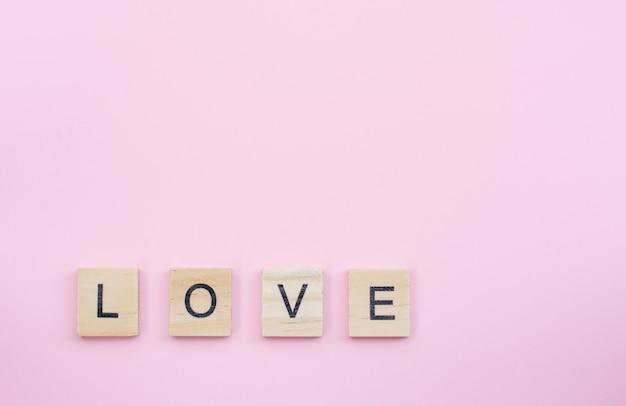 Blocs de bois de texte orthographiant le mot amour sur fond rose