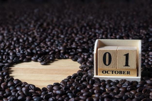 Blocs de calendrier en bois avec groupe de nombreux grains de café sur marbre