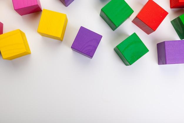 Blocs de construction en bois colorés isolés sur blanc