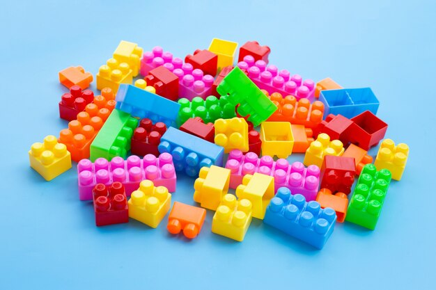 Blocs de construction en plastique sur mur bleu.