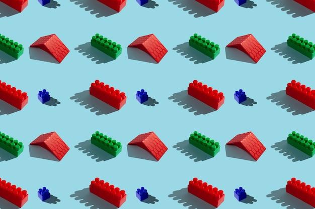 Blocs de construction rouges et verts sur fond bleu, modèle sans couture