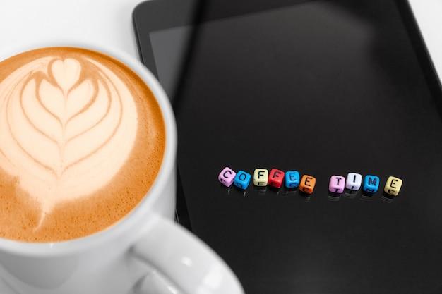 Blocs de cube de lettres avec des concepts de temps de café. café chaud mousseux avec l'art de la feuille.