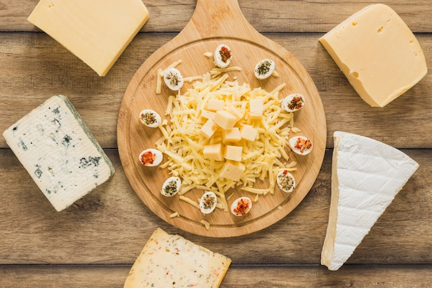 Blocs de fromage entourés près de la planche à découper en bois sur un bureau en bois