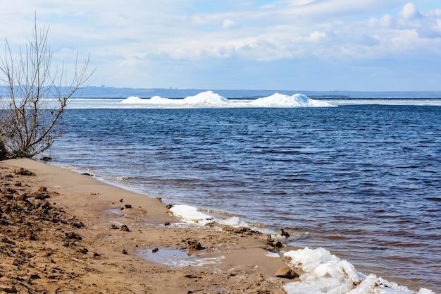 Blocs de glace naturels se brisant contre le rivage au printemps. arctique, hiver, paysage de printemps. la glace dérive le long de la volga.