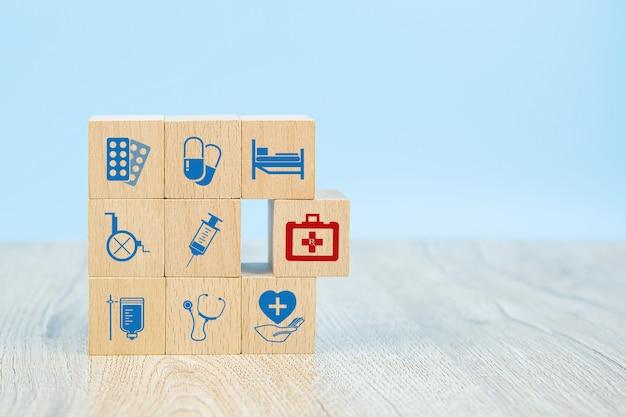 Blocs de jouets en bois en forme de cube empilés avec des icônes de symboles médicaux.