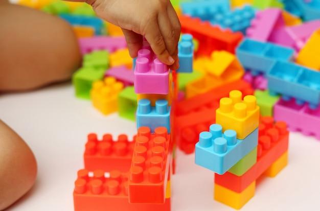 Blocs de jouets en plastique de main de l'enfant avec l'arrière-plan flou