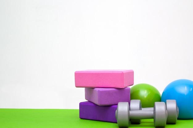 Blocs roses et violets, balles et haltères sur tapis vert.