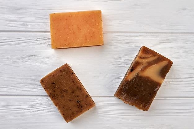 Blocs de savon naturels faits à la main sur fond de bois blanc.