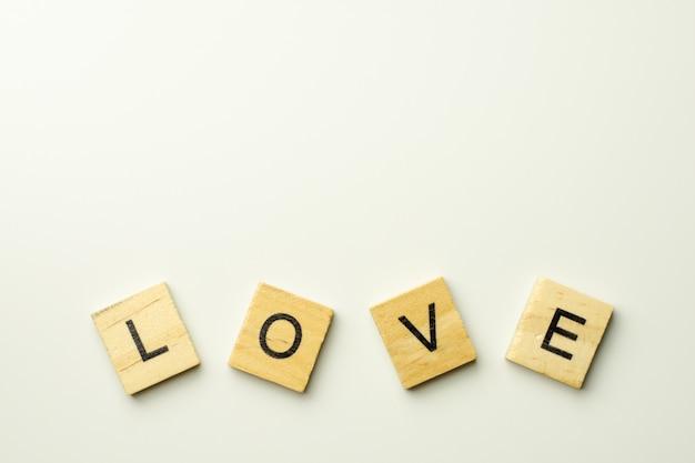 Blocs de texte en bois orthographiant le mot amour sur fond blanc