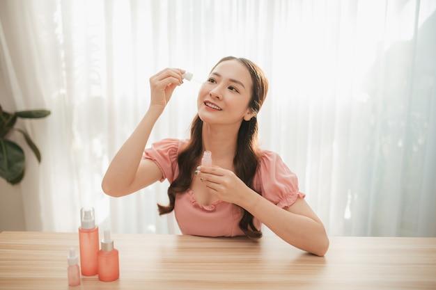 Blog de beauté. tutoriel maquillage et soin du visage. jeune femme séduisante tient dans ses mains un produit de beauté