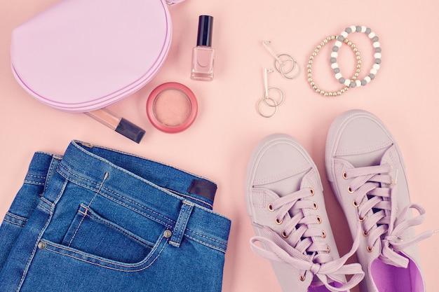 Blog de mode ou concept de magazine. baskets femme rose, jeans et maquillage sur la surface rose pastel mise à plat, vue de dessus