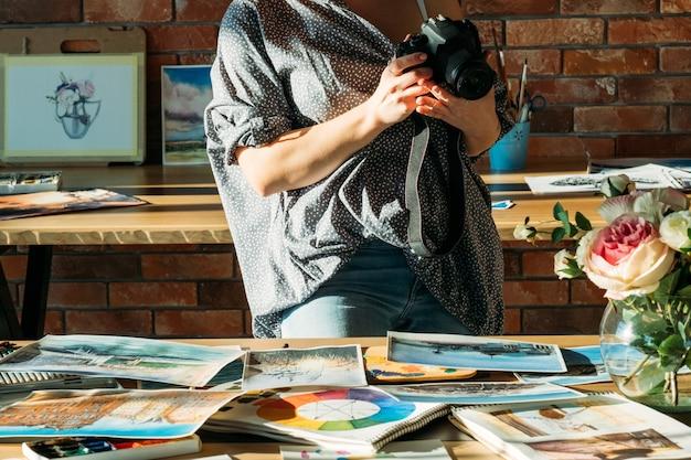 Blog de peinture d'art. espace de travail studio. femme peintre prenant des photos d'œuvres à l'aquarelle.
