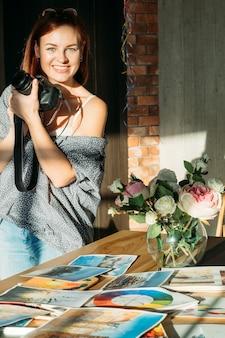 Blog de peinture d'art. espace de travail studio. peintre femme souriante prenant des photos d'œuvres à l'aquarelle.