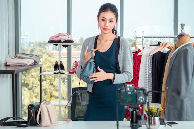 Blog vidéo en direct d'une belle femme asiatique et sac de vente dans les magasins en ligne