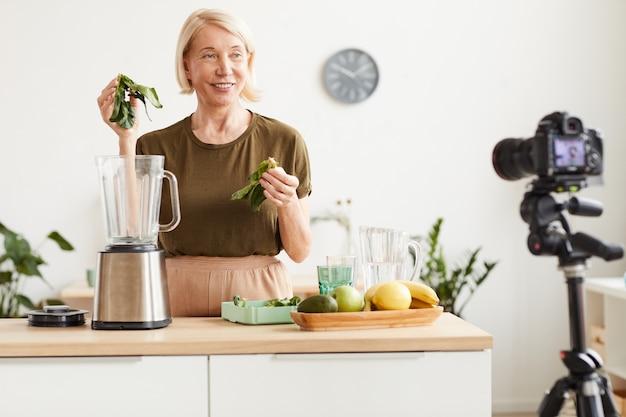 Blogger alimentaire souriant à la caméra et montrant le processus de préparation d'un cocktail sain dans la cuisine