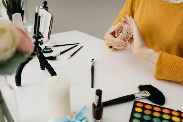 Blogger diffusant du maquillage en ligne avec un smartphone