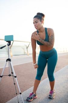 Blogger fait de la vidéo. un blogueur sportif parle de développer ses muscles tout en faisant une vidéo debout à l'extérieur