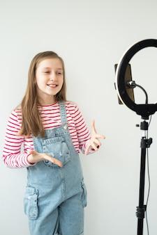 Blogger de médias sociaux adolescente enregistrement vidéo parlant à la recherche de smartphone sur trépied avec anneau lumineux.