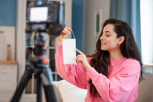 Blogger pointant sur un masque chirurgical devant la caméra