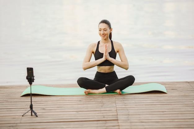 Blogger pratiquant le yoga avancé au bord de l'eau