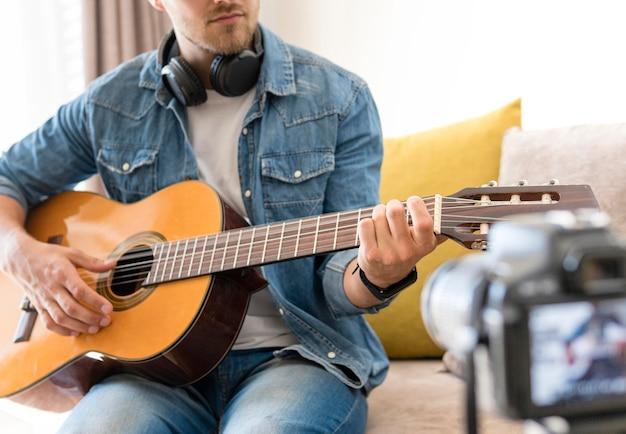 Blogger s'enregistrant tout en jouant de la guitare