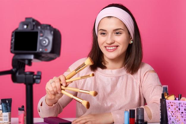 Blogging, technologie moderne et concept de personnes. heureuse femme souriante blogueuse vidéo beauté détient des pinceaux pour le maquillage