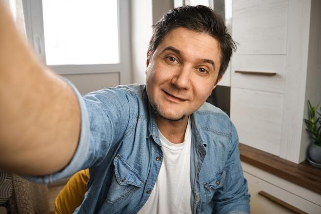 Un blogueur d'âge moyen se capture pour un blog vidéo sur sa chaîne devant la caméra à la maison
