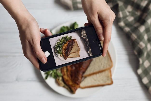 Un blogueur alimentaire prend une photo de son petit-déjeuner, une omelette aux herbes saines
