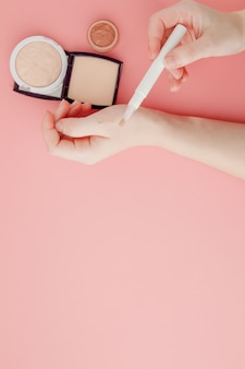 Blogueur beauté femme mains tenant bouteille et tube spa cosmétiques professionnels haut de gamme sur fond rose, concept de minimalisme, tons chaleureux et copyspace