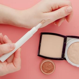 Blogueur beauté femme mains tenant la bouteille et le tube spa cosmétiques professionnels haut de gamme sur une surface rose, concept de minimalisme, tons chauds et copyspace