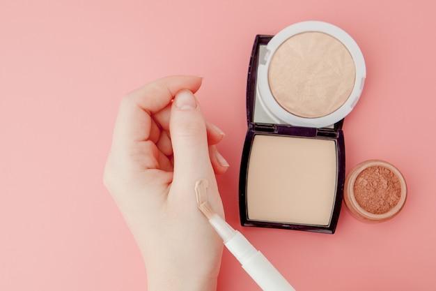 Blogueur beauté femme mains tenant bouteille et tube spa professionnel haut de gamme, concept de minimalisme, tons chauds et copyspace