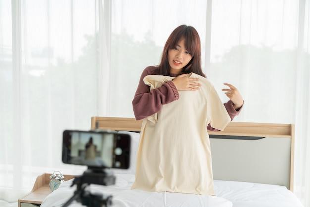Blogueur belle femme asiatique montrant des vêtements à la caméra pour enregistrer une vidéo vlog
