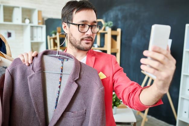 Blogueur branché prenant selfie avec veste