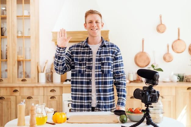 Un blogueur culinaire crée du contenu et regarde la caméra un chef masculin salue ses abonnés