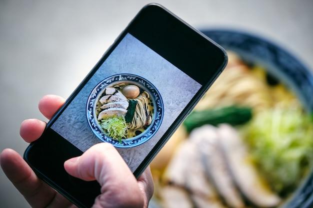 Blogueur de culture prenant une photo de ramen sur un smartphone